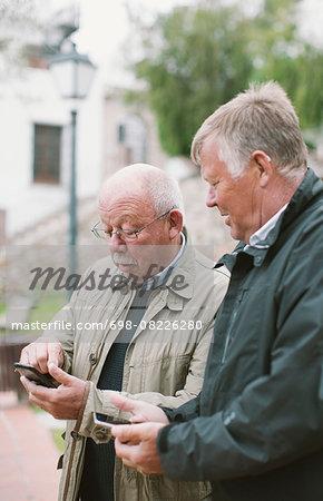 Senior men using smart phones outdoors