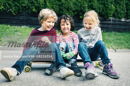 Playful friends sitting on skateboard at yard