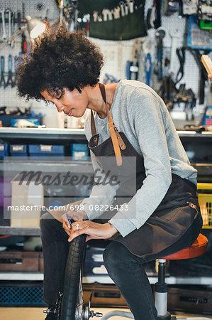Mid adult female mechanic repairing bicycle tire in workshop