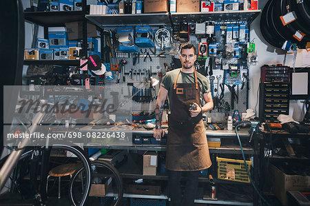 Portrait of confident mechanic at workbench