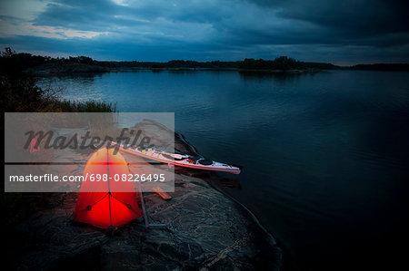 Tent and kayak at lakeshore during dusk
