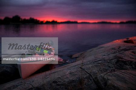 Kayak at lakeshore during sunset