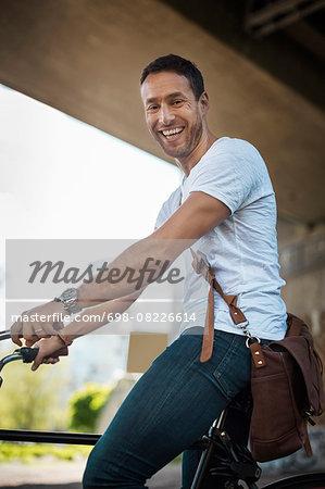 Portrait of happy businessman with bicycle under bridge
