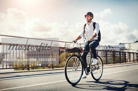 Businessman riding bicycle on bridge against sky