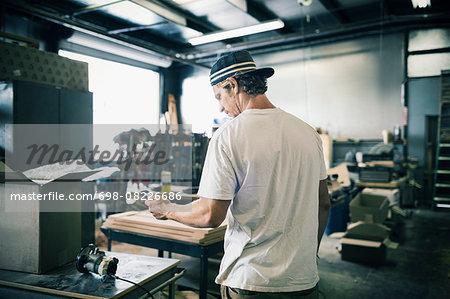 Carpenter using mobile phone in workshop