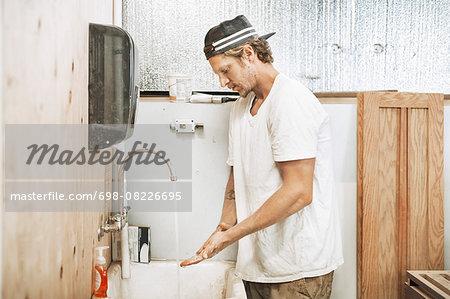 Carpenter washing hands in workshop
