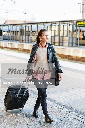 Full length of businesswoman pulling wheeled luggage while walking on railroad station platform
