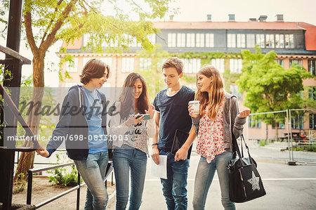 Happy teenagers using smart phone on street