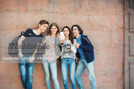 Happy teenagers taking selfie against wall