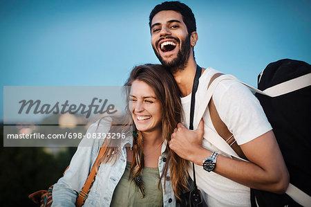 Happy tourist couple enjoying against clear blue sky