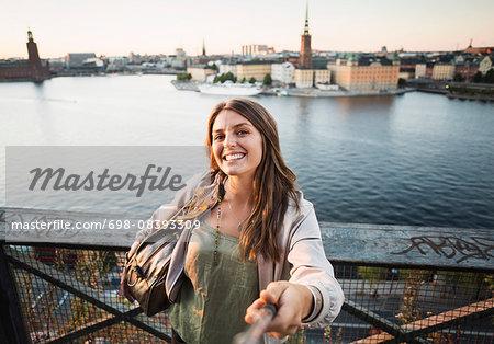 Portrait of happy female tourist holding monopod on bridge by river