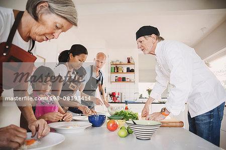 Senior man guiding family in preparing Asian food at kitchen