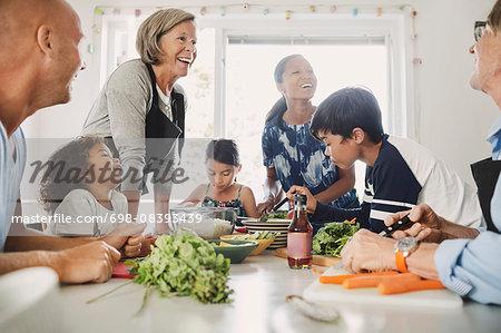 Happy multi-ethnic family preparing Asian food at kitchen