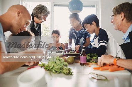 Multi-ethnic family preparing Asian food at kitchen