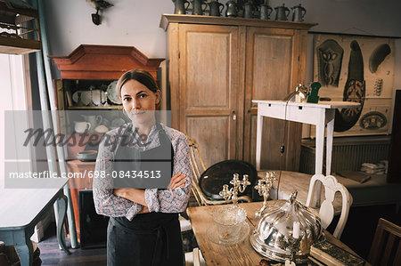 Portrait of confident female owner standing in antique shop