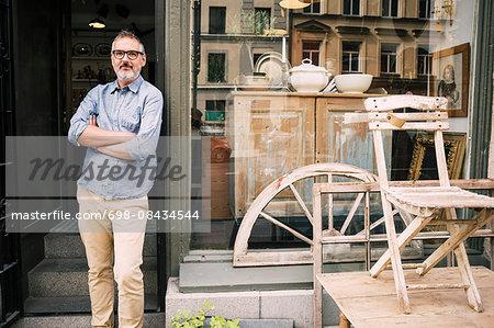 Confident owner standing on entrance of antique shop