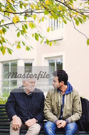 Caretaker communicating with senior man while sitting on bench