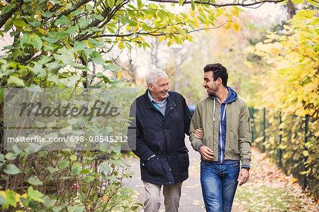 Happy senior man with caretaker walking in park