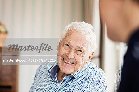 Happy senior man looking at caretaker in nursing home
