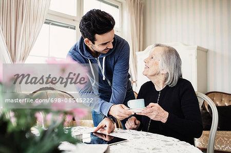 Happy caretaker serving coffee to senior woman in nursing home