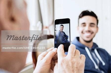 Senior man photographing caretaker through mobile phone
