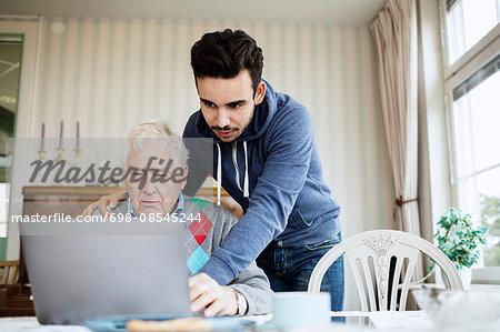 Caretaker assisting senior male in using laptop at nursing home