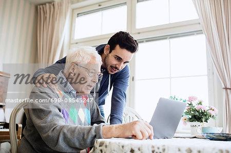 Caretaker and senior man using laptop in nursing home