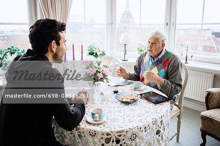 Senior man communicating to caretaker at dining table in nursing home