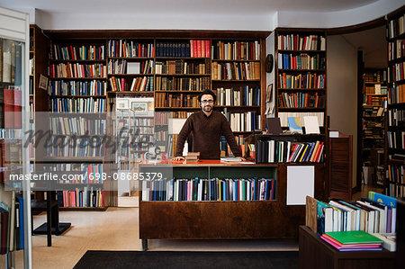 Portrait of owner standing against bookshelves in library