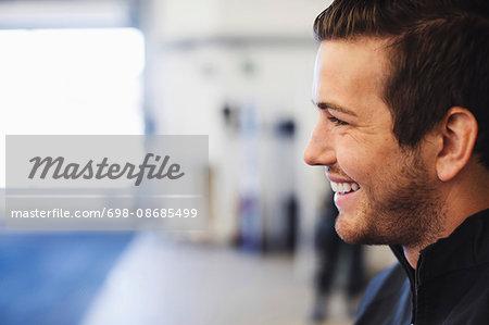 Profile view of happy mechanic in auto repair shop