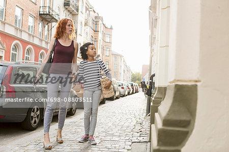 Woman walking with girl on sidewalk in city