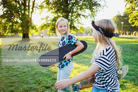 Smiling friends carrying skateboards walking on grassy field