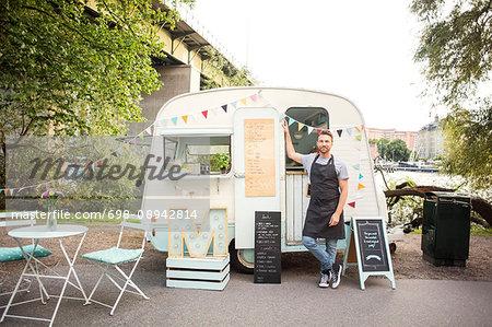 Full length portrait of confident owner standing outside food truck on street