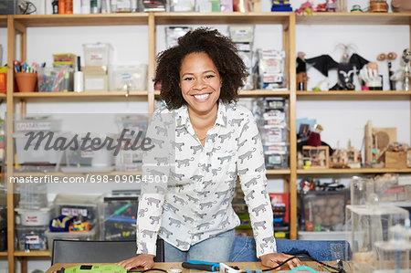 Portrait of confident female technician standing against shelf at workshop