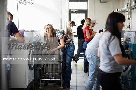 Multi-ethnic university students using washing machines in laundromat