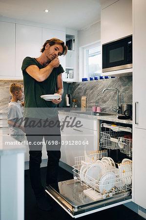Man talking on mobile phone while using dishwasher at kitchen