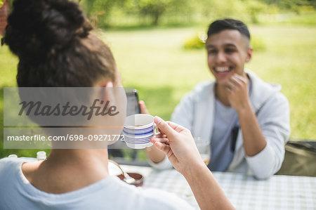 Smiling teenage boy looking at female friend drinking coffee in restaurant