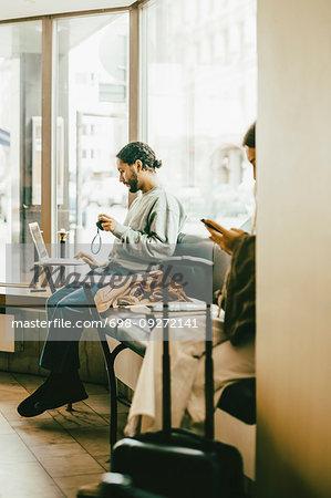 Full length of man using laptop while sitting in restaurant