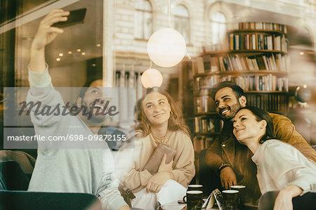 Friends taking selfie while sitting in restaurant seen through glass