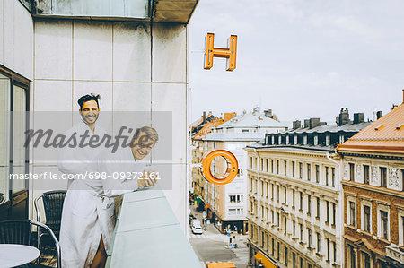Smiling gay couple enjoying in hotel balcony