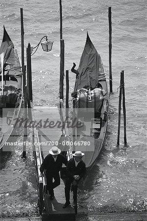 Two Gondoliers Standing near Gondolas, Venice, Italy