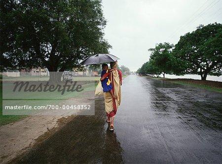 Mother and Child Walking in Rain, Calcutta, India - Stock