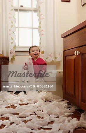 Child Unrolling Toilet Paper In Bathroom