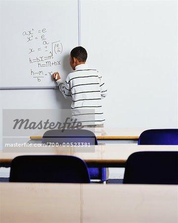 Boy Solving Math Problems on Whiteboard