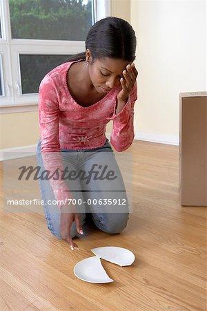 Woman Picking up Broken Plate
