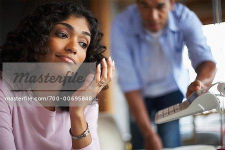 Man Passing Adding Machine to Woman