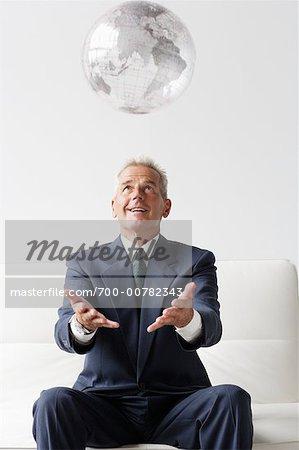 Businessman Throwing Globe