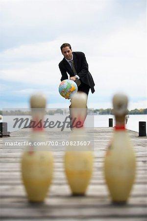Businessman Bowling With Globe