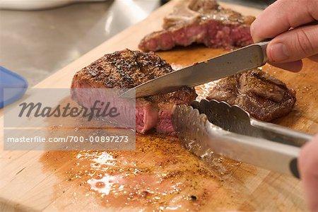 Close Up of Man Cutting Steak