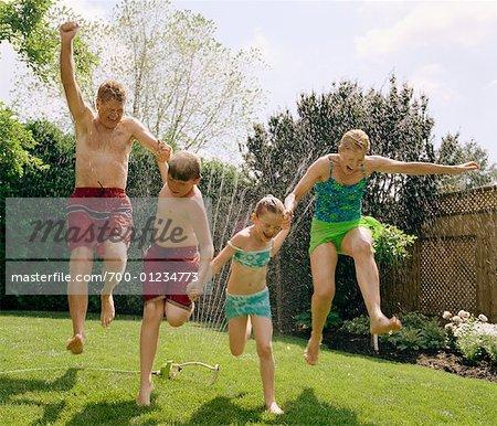People Jumping Through Sprinkler
